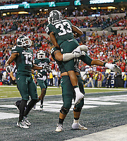 Michigan State Spartans running back Jeremy Langford (33) celebrates his fourth quarter TD with teammates Michigan State Spartans wide receiver Bennie Fowler (13) and Michigan State Spartans guard Adam Brown (57) to seal a victory over Ohio State in the Big 10 Championship game  at Lucas Oil Stadium in Indianapolis, Ohio on December 7, 2013.  (Chris Russell/Dispatch Photo)