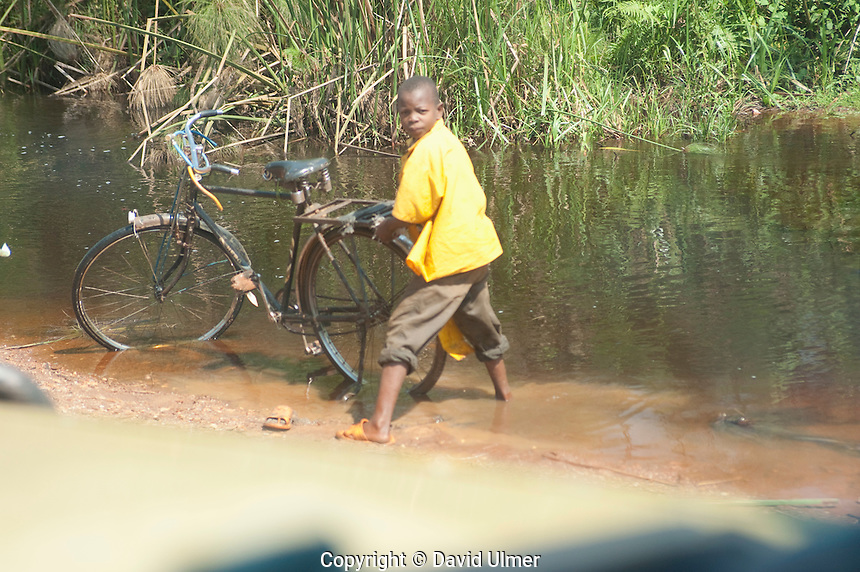Boy washes his bicycle in a stream next to the road. Uganda