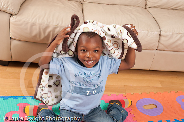 Three year old boy playing peek a boo with blanket on his head horizontal portrait