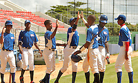 "Major League Baseball prospect Roberto Caro celebrates his run with team mates during the final game of the ""Torneo Supremo"" at the Quiskeya National Stadium in Santo Domingo. The Tournament which aims to maximize the ability of Major League Baseball organizations to scout in the Dominican Republic. According to the MLB's office in the Dominican Republic, this year, the tournament introduced 23 new baseball prospects. July 29 2011. ViewPress/ Kena Betancur"