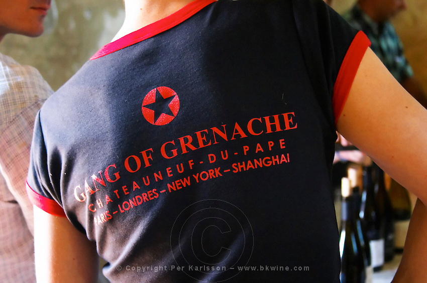 "A wine taster with a black t-shirt tshirt saying ""The Gang of Grenache"" advertising a group of Chateauneuf-du-Pape growers. Rhone. France Europe."