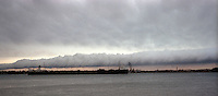 A Great Lakes ship passes Port Huron and Sarnia heading north on the St. Clair River with dramatic clouds on the skyline.