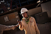 28 year old Chinese engineer, Zhu Haikuo from SEPCO is seen working with Indian engineers at the construction site of the Adani Power plant of 4620 MW capacity in Mundra port industrial city of Gujarat, India. Indian power companies have handed out dozens of major contracts to Chinese firms since 2008. Adani Power Ltd have built elaborate Chinatowns to accommodate Chinese workers, complete with Chinese chefs, ping pong tables and Chinese television. Chinese companies now supply equipment for about 25% of the 80,000 megawatts in new capacity.