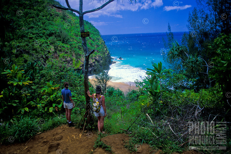 Hikers on Kalalau trail overlooking Hanakapiai beach on the Na Pali coast