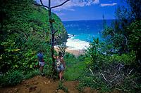 Hikers on Kalalau trail overlooking Hanakapiai beach on the Na Pali coast