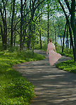 A young woman, dressed in a pink dress walks on a path into the woods.