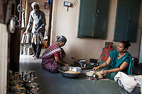 Archana's father-in-law (left) prepares tiffin containers, as she (right) makes bread in her house with her family in Anand, Gujarat, India on 11th December 2012. Archana , an ex-surrogate, continues to work with Dr. Nayana Patel, catering specially prepared tiffin meals to the surrogates and Akanksha IVF and Surrogacy clinic staff. Photo by Suzanne Lee / Marie-Claire France