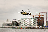 Military rescue helicopter from the Danish Military having a rescue drill at the entrance of the harbour in Aarhus Denmark, with modern architecture in the background