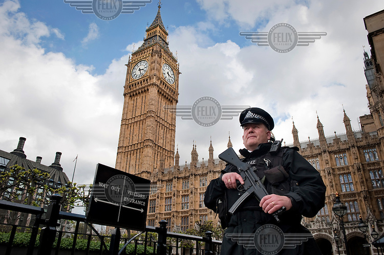 An armed police officer in front of The House of Commons and The Clock Tower in Westminster, London. Although the tower is popularly referred to as Big Ben, this is actually the nickname of the bell housed within whose official name is the Great Bell.