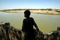 As Samawah--Sadiq Nahi, 12, looks out over the river in the town of 180,000 that spills over into both side. As Samawah located about 180 Kilometers south of Baghdad was a town that suffered many setbacks during the war and is now on its way to rebuilding. There has been many obstacles for the people as they grow more and more impatient with the progress at the speed the US Military are carrying out civil affairs. .EDS NOTE: For story BY MEGAN STACK about As Samawah and the daily life in the city during this difficult time.
