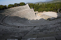 EPIDAURUS, GREECE - APRIL 14 : A panoramic view from above of the Theatre, on April 14, 2007 in Epidaurus, Greece. The Theatre, designed by Polykleitos the Younger, was built in the late 4th century BC and extended in the Hellenistic period. It was rediscovered in 1881 and significantly restored in the 1950s.  It has the three main features of a Greek theatre: the orchestra, a sunken round stage; the skene, a raised rectangular stage; and the cavea, a raked semi-circular auditorium with radiating diazomas. The theatre is renowned for its accoustics thanks to the symmetry of the cavea, and for its beautiful mountain view, seen in the early morning light, with shadows cast across the theatre. (Photo by Manuel Cohen)