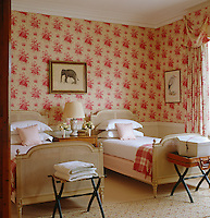 This twin bedroom is furnished with a pair of French cane beds