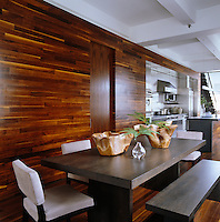The walls and floor of the kitchen-diner are covered in American walnut