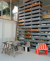 Industrial designer Stefan Diez's studio with prototypes of a couple of his chairs in front of a large floor-to-ceiling shelving unit