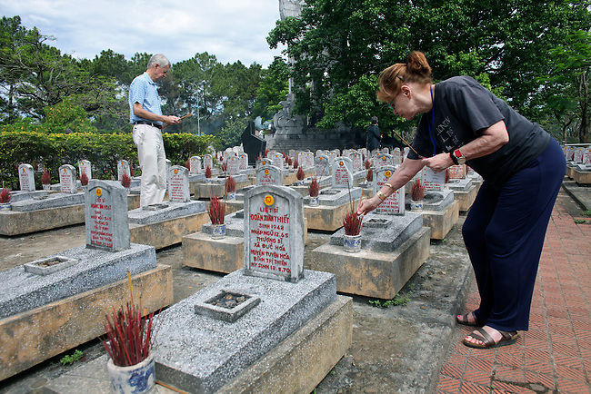 Chuck Searcy and Myra MacPherson, of Veterans for Peace, place burning incense sticks on the graves of Vietnamese solders at Truong Son Martyrs Cemetery in Quang Tri province, Vietnam. The cemetery contains the graves of about 10,300 communist soldiers who died along the Ho Chi Minh Trail supply network into South Vietnam during the conflict from 1959 to 1975. April 24, 2013.