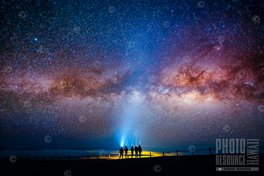 Visitors' headlights beam up through the Milky Way Galaxy that fills the night sky overhead, Big Island.