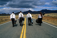Group of musicians walking down a deserted highway with instruments in hand.