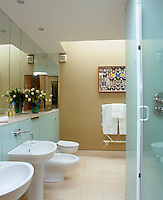 The walls of this bathroom are of opaque glass and mirror and the floors are limestone