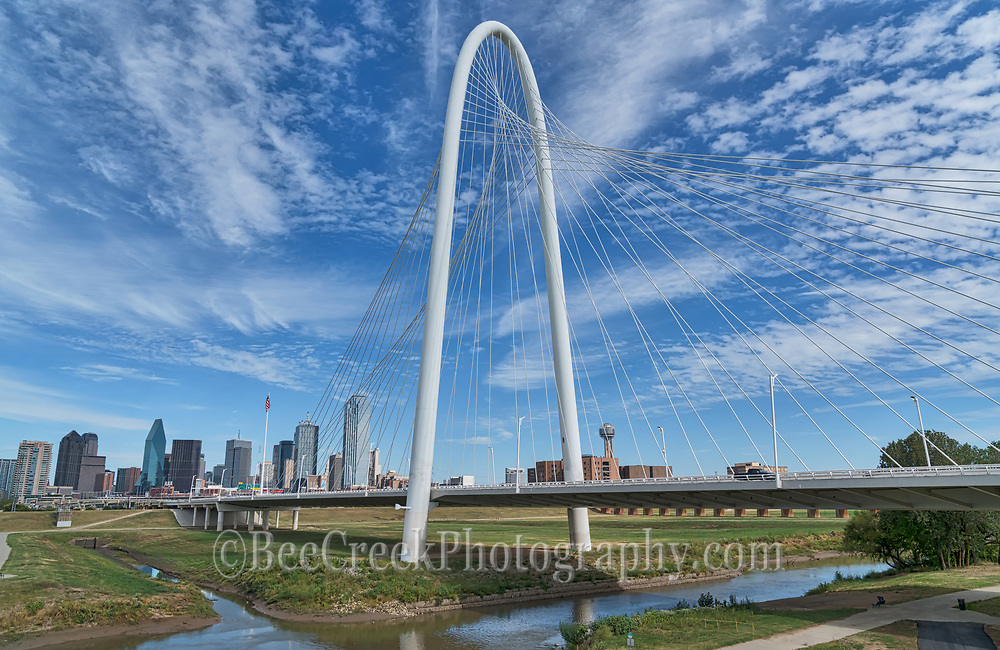 A beautiful blue sky day with nice clouds in downtown Dallas with the Margaret Hunt Hill Bridge along the Trinity River and the cityscape of the buildings in the downtown area of the city.