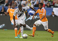 CARSON, CA - DECEMBER 01, 2012:   Edson Buddle (14) of the Los Angeles Galaxy breaks past Boniek Garcia (27) and Corey Ashe (26) of the Houston Dynamo during the 2012 MLS Cup at the Home Depot Center, in Carson, California on December 01, 2012. The Galaxy won 3-1.