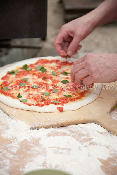 Adding fresh herbs to a pizza already topped with tomato sauce. olive oil, and shaved garlic.