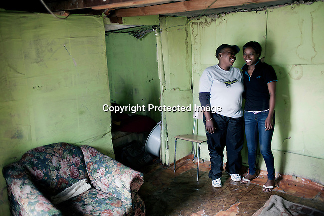 CAPE TOWN, SOUTH AFRICA - OCTOBER 19: Phato Mkhosana with her girlfriend Brenda Tahabatha in their house on October 19, 2011 in Khayelitsha outside Cape Town, South Africa. Cape Town is a city known for tolerating gays and lesbians except in the townships where they get harassed and often attacked. Some women have been raped in so called corrective rape, where men rapes them to make them women again. They can't show their love freely on the streets in the townships so they usually have to meet in houses and this bar.  (Photo by Per-Anders Pettersson)