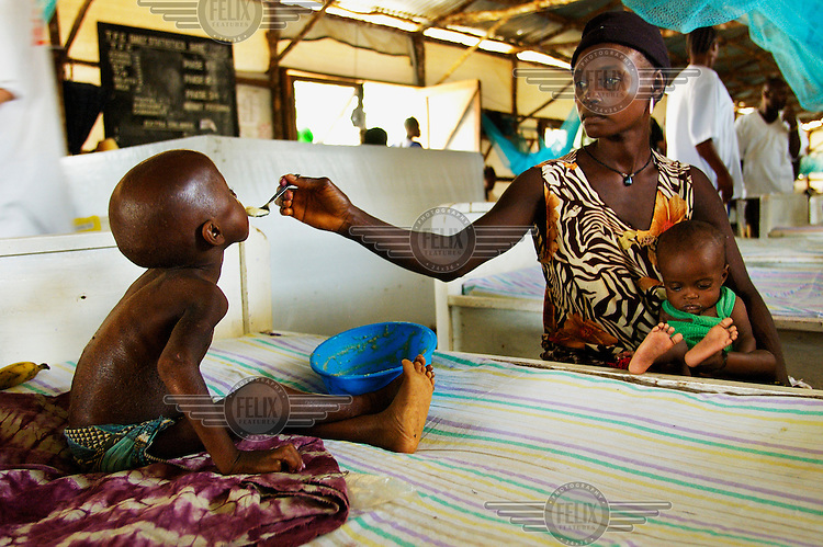 Twenty-five-year-old Hawa Konay feeds her seven-year-old son, Malegi Nabi, in the therapeutic feeding centre at Gondoma Clinic. The centre, which is supported by the aid agency Medecins Sans Frontieres (MSF), treats children who are severely malnourished. These children are often referred here after attending the clinic for other illnesses..