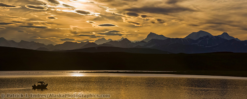 Sport fishermen troll for lake trout on a summer evening. Summit Lake and the panorama of the Alaska Range in the distance, Interior, Alaska.