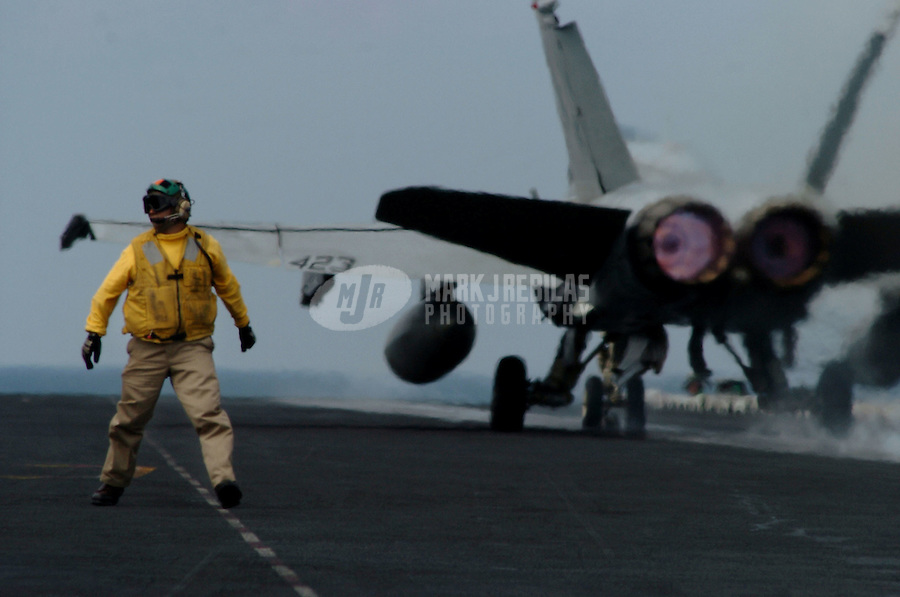 """040906-N-6213R-002 South China Sea (Sept. 6, 2004) - A flight deck crewmember looks on as an F/A-18C Hornet from the """"Fist of the Fleet"""" of Strike Fighter Squadron Two Five (VFA-25) launches from aboard USS John C. Stennis (CVN 74) to participate in a scheduled mission. USS John C. Stennis with Carrier Air Wing Fourteen (CVW-14) embarked, are currently participating in a scheduled deployment to the western Pacific Ocean. Photo by Mark J. Rebilas"""