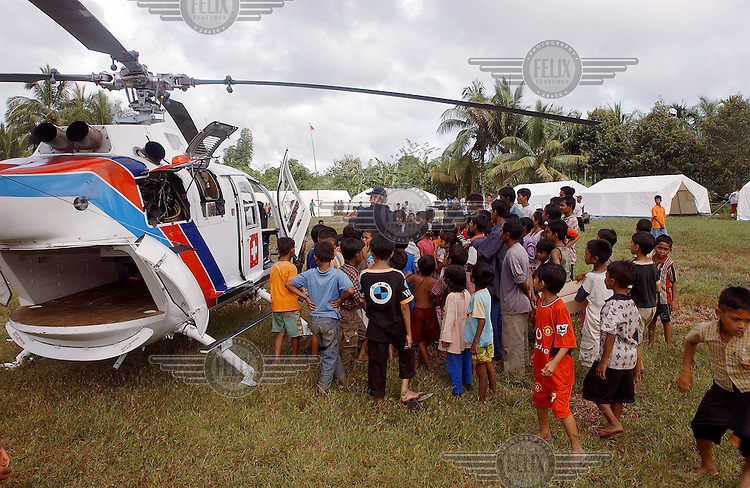 The German Red Cross establish a basic health care unit in the town of Teunom following the tsunami which struck South Asia on 26/12/2004. Their 44 tonne cargo is flown down by the US military, and the personnel fly with Helimissions..An underwater earthquake measuring 9 on the Richter scale triggered a series of tidal waves which caused devastation when they struck dry land. 12 countries were affected by the tsunami, with a combined death toll of over 150,000. Aceh, the closest landfall to the epicentre of the quake, suffered the greatest loss of life. Photo: Dermot Tatlow/Panos Pictures/Felix Features