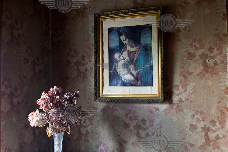 A painting on a wall and flowers in the apartment of an injecting drug user in Tbilisi.