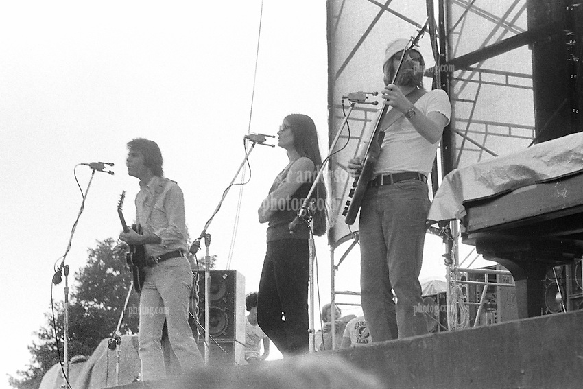 Bob Weir, Donna Godchaux and Phil Lesh performing with The Grateful Dead in Concert at Dillon Stadium on 31 July 1974. Jerry Garcia is partially blocked from view and Ned Legin is in the background looking on. Photograph taken with a Nikon FTn Camera and Kodak Tri-X B&W Film.