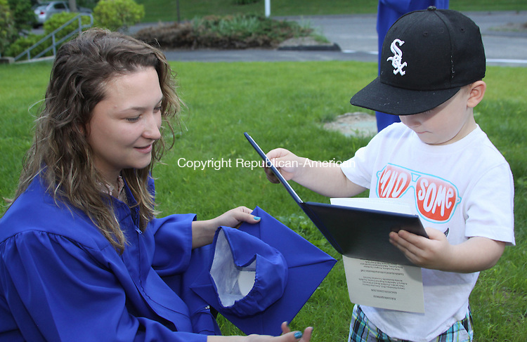 LITCHFIELD,CT - 17 June 2014 - 061714JM03 - Trevor Pelkey, 2, checks out the high school diploma his mom, Katarina Pelkey of Torrington, left, earned at the Foothills Adult &Continuing Education program graduation at Education Connection in Litchfield on Tuesday. John McKenna Photo