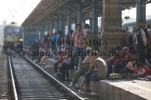 Illegal migrants sit on the platform edge next to a stopped engine as they wait to board a train at the main railway station Keleti in Budapest, Hungary on September 03, 2015. ATTILA VOLGYI