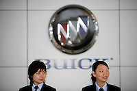 Sales reps stand in front of a Buick logo at a Buick dealership owned and operated by Dongchang Autos in Shanghai, China.Shanghai General Motors (Shanghai GM), Buick's manufacturer in China has just announced a new Chinese market exclusive Buick Park Avenue in the same month. Since 1999 when the Buick Regal was first sold under Shanghai GM, Buick has been one of the most popular automobile brands in China..