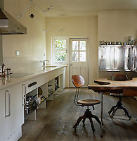 In this kitchen, stainless steel storage cupboards and white kitchen units contrast with a limed oak floor and antique table and chairs