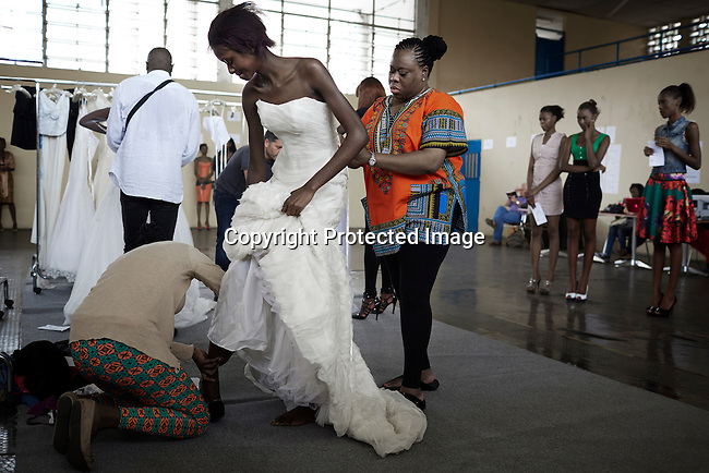 KINSHASA, DRC - JULY 17: Model Vanessa Nsul Kilem, age 21, fits a wedding dress for the Nigerian London based designer Yemi Osunkoya a day before Kinshasa Fashion Week on July 17, 2014, at the boxing gym at Shark club in Kinshasa, DRC. Vanessa dreams of becoming a super model. She has won local beauty pageants and she was one of 2000 girls casting for the thirty spots to participate in Local and invited foreign-based designers showed their collections during the second edition of Kinshasa Fashion week. (Photo by Per-Anders Pettersson)