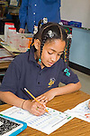 Black 7+ girl with multiple braids in uniform writes on test in second grade class in school in Avondale suburb, New Orleans