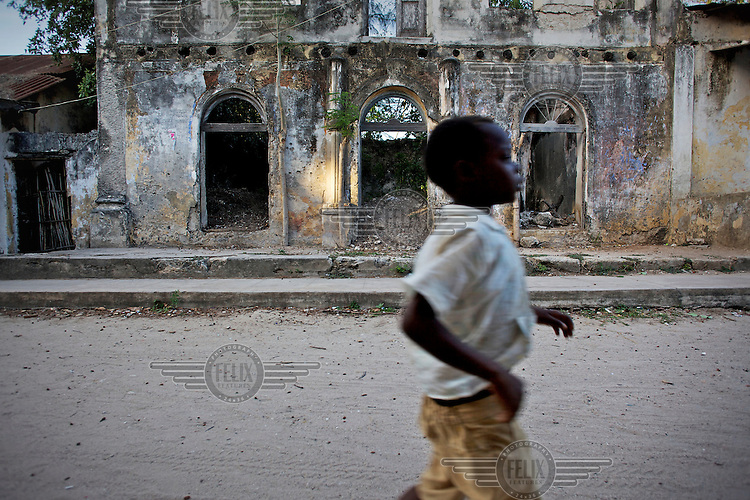 A child runs past deserted buildings on a street in the town of Ibo on Ibo Island.