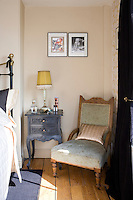 In the master bedroom a vintage bedside table next to an antique chair re-upholstered in a pretty floral brocade in a subtle shade of eau-de-nil