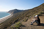 A female hiker rests and takes in the scenery of the Pacific Ocean during a hike in Point Mugu State Park, California, USA
