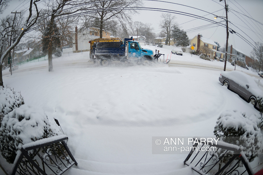 A snowplow from Town of Hempstead, Long Island, plows street as snow falls again on the South Shore, where highest amounts are expected in region, creating hazardous conditions during morning traffic rush. 180 degree fisheye view, seen from front entrance of suburban home. Temperature is 18 degree Fahrenheit, and snow accumulation of 3 to 5 inches is predicted in L.I., New York City, and nearby Northeast areas. Winter Weather Advisory remains in effect until noon from National Weather Service.