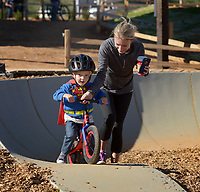 NWA Democrat-Gazette/BEN GOFF @NWABENGOFF<br /> Kamie Saylor of Springdale helps her son Lincoln Saylor, 3, ride his strider bike around the pump track on Saturday Nov. 7, 2015 during opening day of The Railyard bike park in Rogers.