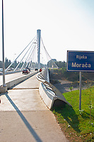 The Millennium Bridge is a cable stayed bridge that spans Moraca River with cables that form a graphic pattern and a single central supporting column. Road sign saying River Moraca. Podgorica capital. Montenegro, Balkan, Europe. Designed by Mladen Ulicevic.