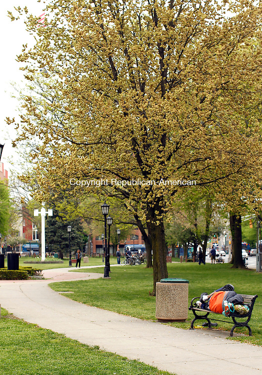 Waterbury, CT-05 May 2012-050512CM03-  A man sleeps on a park bench on the Waterbury city green Saturday afternoon.  The city is looking to revitalize the green which could bring significant change.   Christopher Massa Republican-American