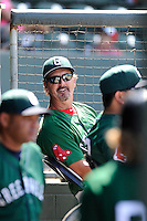 Pitching coach Paul Abbott (48) of the Greenville Drive looks out at the dugout at the beginning of a game against the Savannah Sand Gnats on Sunday, June 22, 2014, at Fluor Field at the West End in Greenville, South Carolina. Greenville won, 7-3. (Tom Priddy/Four Seam Images)
