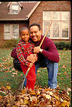 portrait of father and young son raking leaves