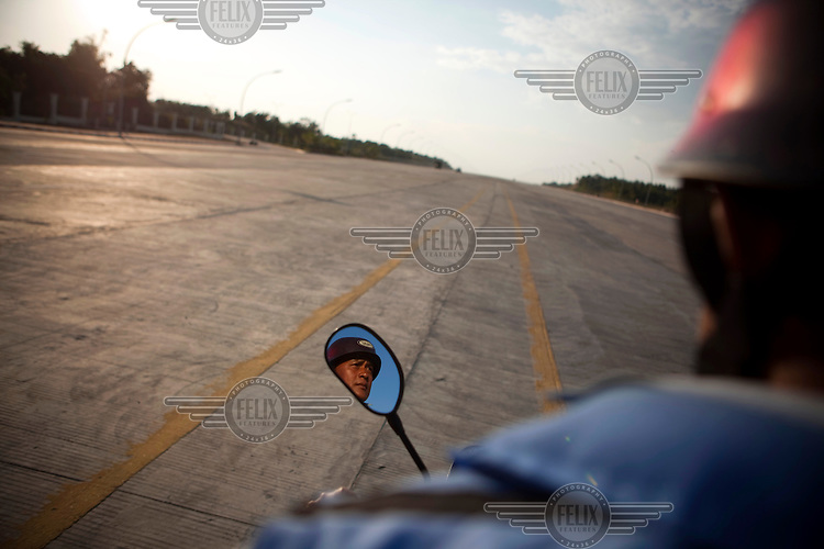 A motorbike taxi driver is seem reflected in the mirror of his motorbike as he drives down an empty street in Naypyitaw, the new capital of Burma (Myanmar) since November 2005.