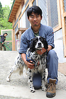 A worker with a dog rescued from the nuclear evacuation zone by ARK animal refuge outside Osaka, Japan, 26th May 2011.  ARK has rescued more than 200 dogs, 16 cats and a guinea pig from with-in the nuclear exclusion zone surrounding the Fukushima Daiichi nuclear power plant in Japan...© Richard Jones/ sinopix.PHOTO BY SINOPIX