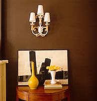 A piece of modern art and a yellow vase stand on a console table beneath a wall sconce in the aubergine coloured living room